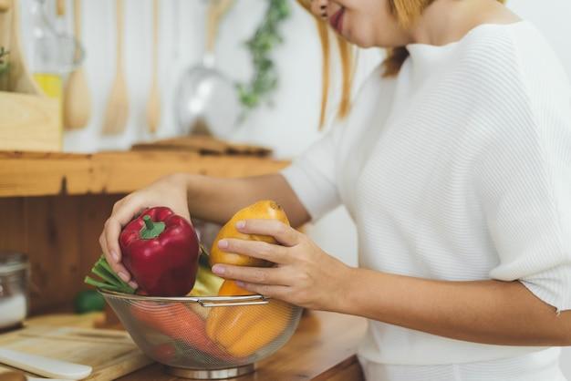 Aziatische vrouw die gezond voedsel maken die zich het gelukkige glimlachen in keuken bevinden die salade voorbereiden
