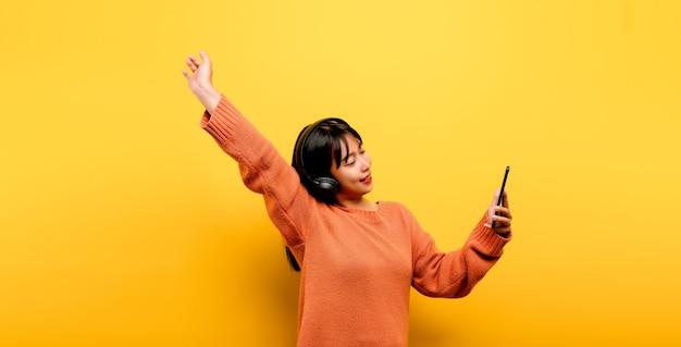 Aziatische vrouw die graag de telefoon gebruikt en naar muziek luistert. ontspannen met muziek. op een comfortabele dag. dans en ontspanning concept. online naar muziek luisteren