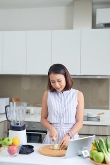 Aziatische vrouw die groenten in keuken snijdt met tablet voor haar
