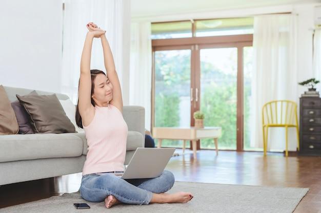 Aziatische vrouw die haar armen strekt om te ontspannen na thuis werken via laptop in de woonkamer thuis