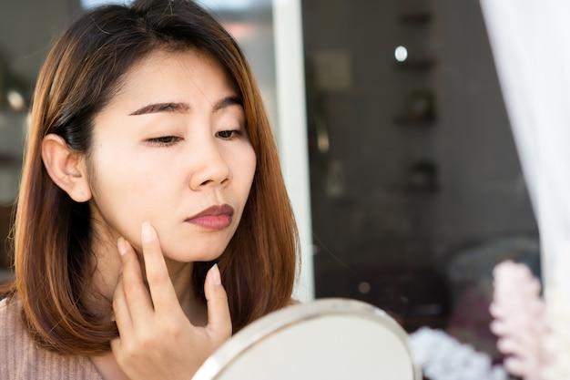Aziatische vrouw die haar droge, donkere kleurenlippen op spiegel controleert