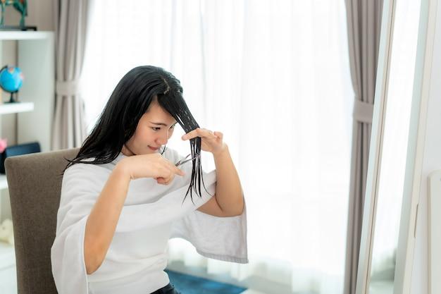 Aziatische vrouw die haar haar zelf knipt met een knipschaar, ze blijven thuis en schuilen op hun plaats tijdens de isolatie van het huis tegen nieuw coronavirus of covid-19