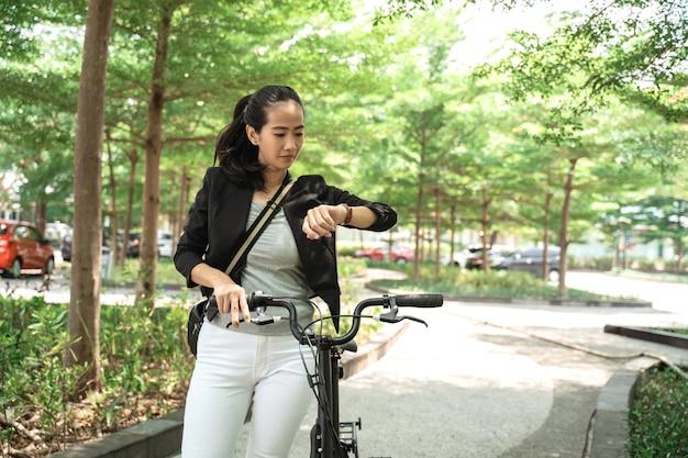 Aziatische vrouw die haar horloge kijkt wanneer met vouwfiets loopt