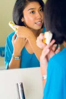 Aziatische vrouw die haar in badkamersspiegel kamt
