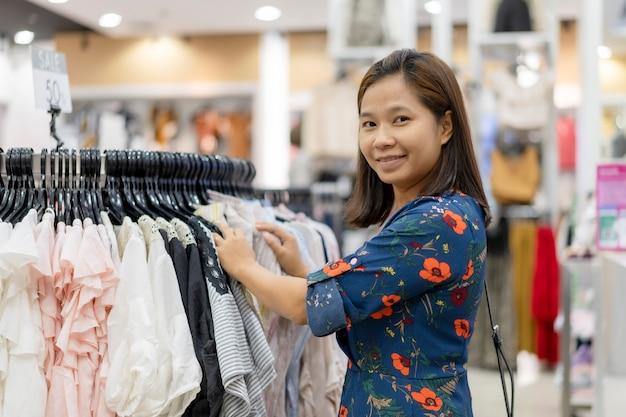 Aziatische vrouw die haar kleren van de manieruitrusting in kast kiezen bij opslag.