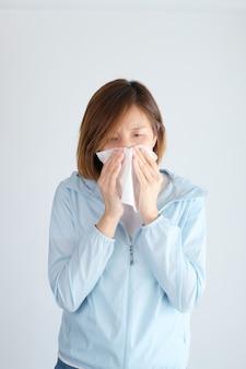 Aziatische vrouw die haar neus blaast