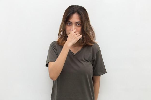 Aziatische vrouw die haar neus wegens een slechte geur houdt