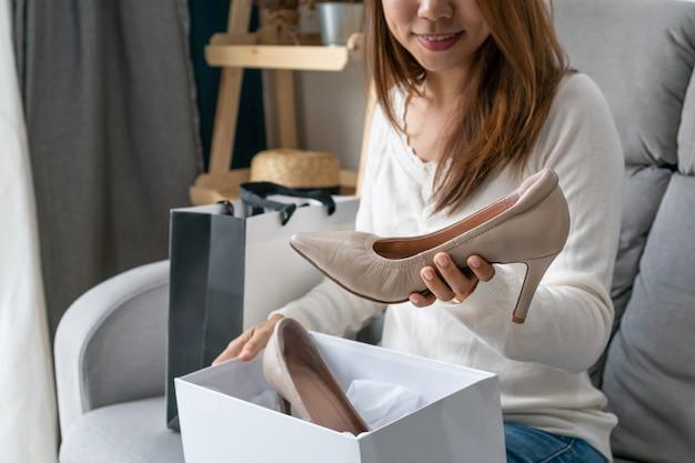 Aziatische vrouw die haar nieuwe hoge hielschoen bekijken en thuis op bank zitten, digitale levensstijl met technologie, elektronische handelconcept