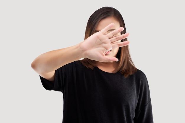 Aziatische vrouw die haar ontkenning op een grijze achtergrond toont. vrouw gebaart een nee-teken.