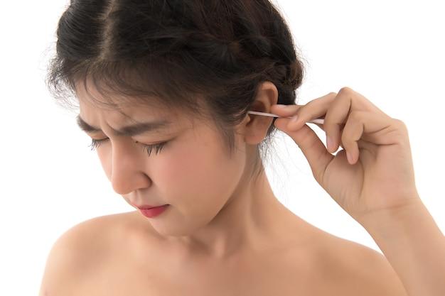 Aziatische vrouw die haar oor met hygiënische zwabber daarin plukt.