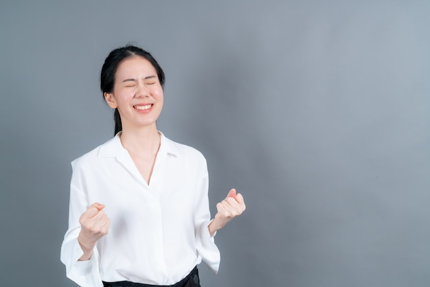 Aziatische vrouw die haar succes en overwinning verheugt die haar vuisten met vreugde balde. gelukkige vrouw die gelukkig is om haar doel en doelen te bereiken. positieve emoties, gevoelens op grijze muur