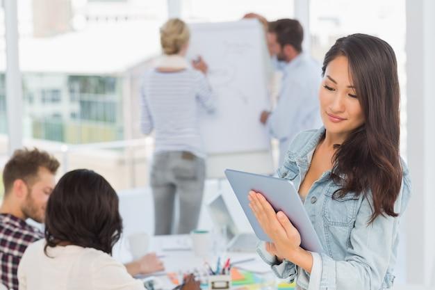Aziatische vrouw die haar tabletpc met behulp van terwijl haar collega's werken