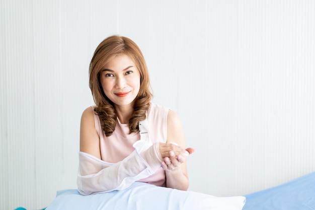 Aziatische vrouw die haar wapen bekijkt dat van ongeval verwondde. concept van gezondheidszorg en wellness bij volwassen mensen.