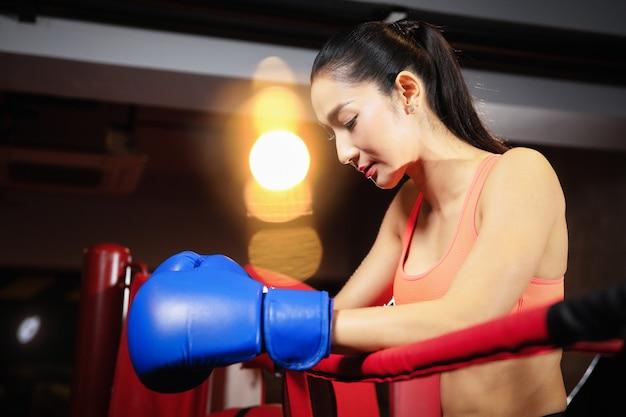 Aziatische vrouw die haar wapens rusten op het touw van boksring tijdens onderbrekingen die in de gymnastiek opleiden