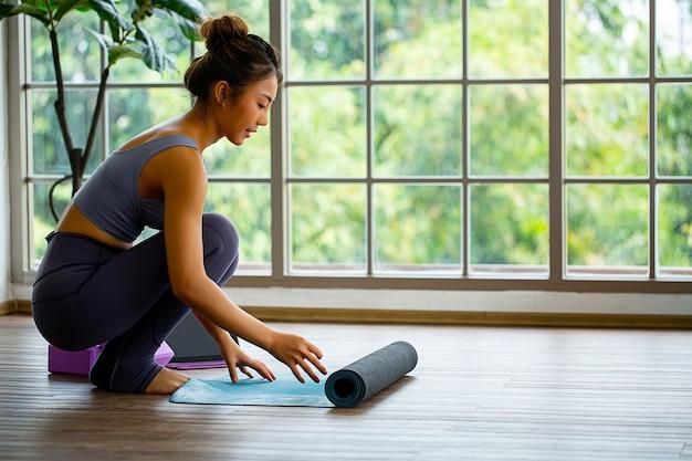 Aziatische vrouw die haar yogamat rolt om thuis te oefenen.