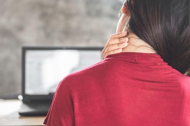 Aziatische vrouw die halspijn heeft die aan computer werkt