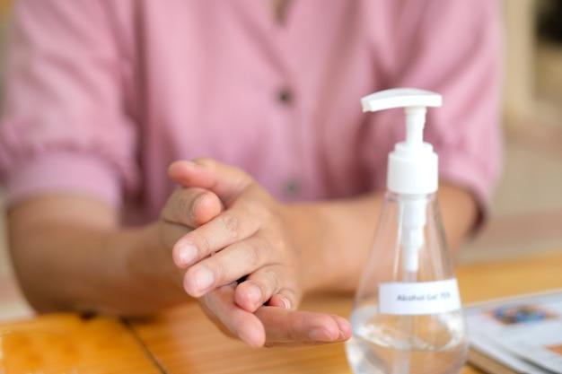 Aziatische vrouw die handdesinfecterend middel gebruikt door alcoholgel te pompen