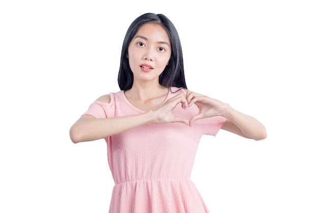 Aziatische vrouw die hartvorm met handen toont die over witte achtergrond wordt geïsoleerd