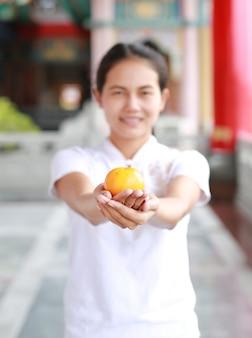 Aziatische vrouw die heilige sinaasappel houden bij chinese tempel in bangkok, thailand