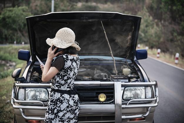 Aziatische vrouw die hersteller of verzekeringspersoneel roepen om een motor van een autoprobleem op een lokale weg te bevestigen