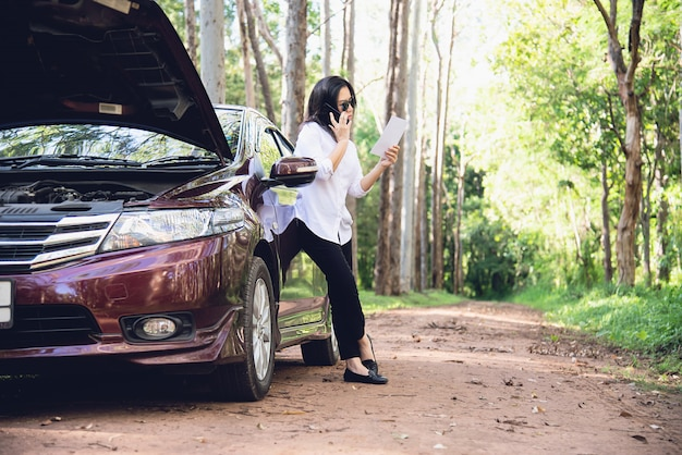 Aziatische vrouw die hersteller of verzekeringspersoneel roept om een motor van een autoprobleem op een lokale weg te bevestigen