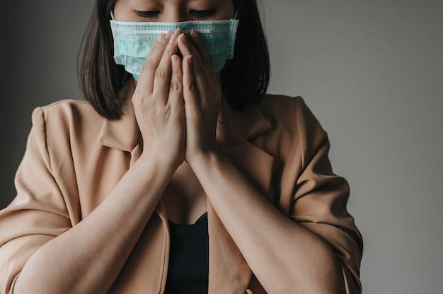 Aziatische vrouw die het beschermende gezichtsmasker hoesten dragen