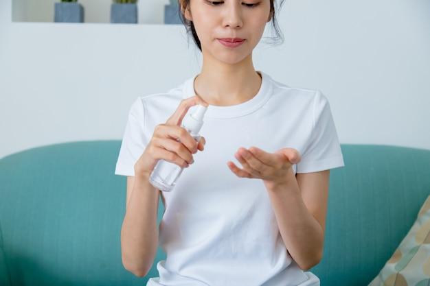 Aziatische vrouw die het handdesinfecterend middel van het alcoholgel gebruikt