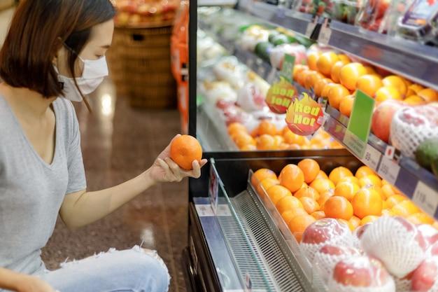 Aziatische vrouw die het medische masker winkelen draagt