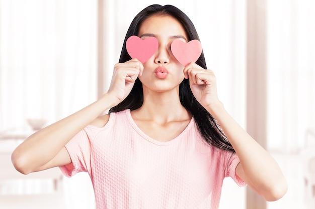 Aziatische vrouw die het rode hart thuis houdt. valentijnsdag