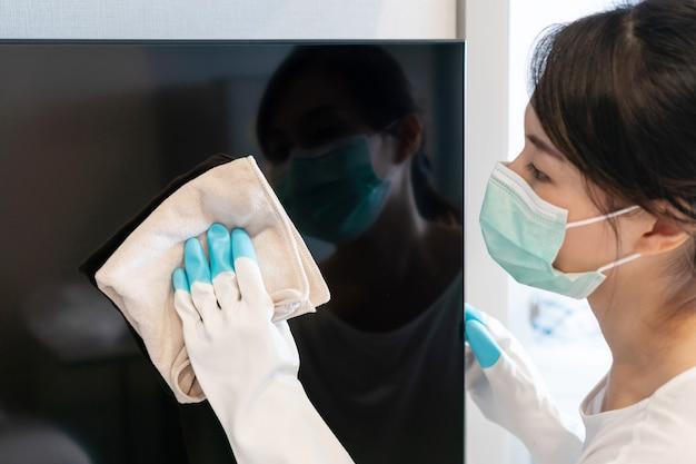 Aziatische vrouw die het tv-scherm thuis schoonmaakt van stof. scherm schijnt. regelmatig opruimen concept. detailopname