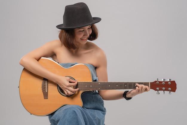 Aziatische vrouw die hoed draagt die haar gitaar speelt
