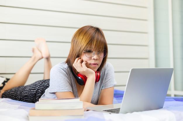 Aziatische vrouw die hoofdtelefoon dragen die met laptop in slaapkamer thuis werken, het werk van huisconcept.
