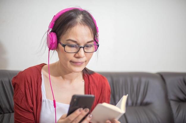 Aziatische vrouw die hoofdtelefoons draagt die bijbel op smartphone lezen