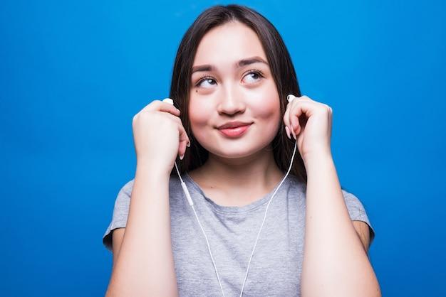 Aziatische vrouw die hoofdtelefoons draagt en aan muziek luistert die op een blauwe muur wordt geïsoleerd