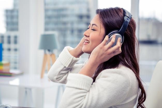 Aziatische vrouw die hoofdtelefoons in bureau met behulp van