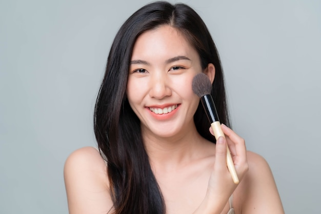 Aziatische vrouw die hyaluron serum op haar gezicht aanbrengt met pipet