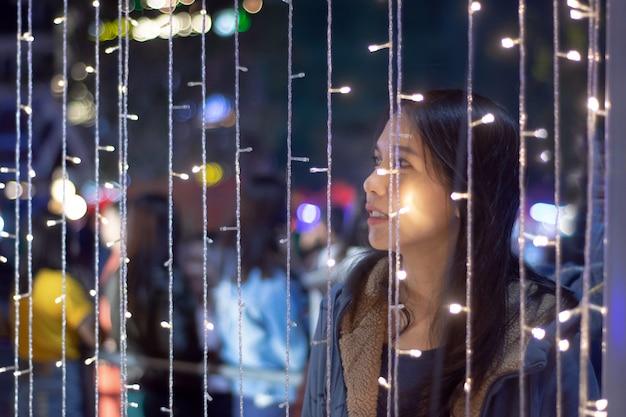 Aziatische vrouw die iets op een achtergrond met bokehkleurlichten bekijkt