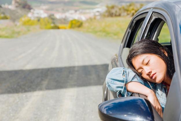 Aziatische vrouw die in auto tijdens roadtrip dutten