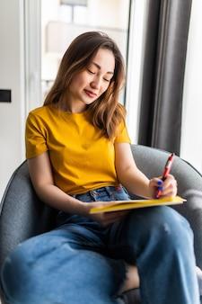 Aziatische vrouw die in blocnote schrijft die op witte moderne stoel wordt geplaatst