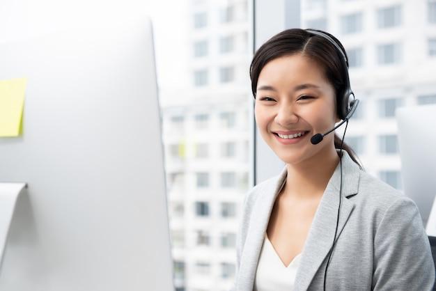 Aziatische vrouw die in call centrebureau werkt