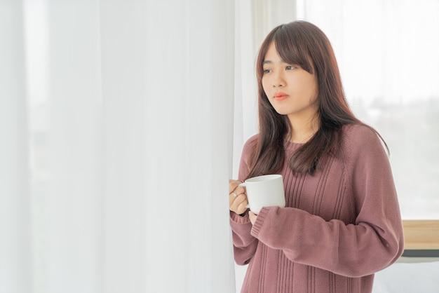 Aziatische vrouw die in de ochtend koffie drinkt