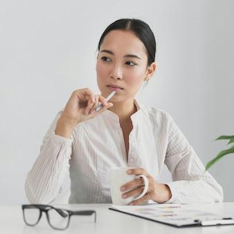 Aziatische vrouw die in het bureau denkt