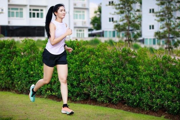 Aziatische vrouw die in het stadspark loopt