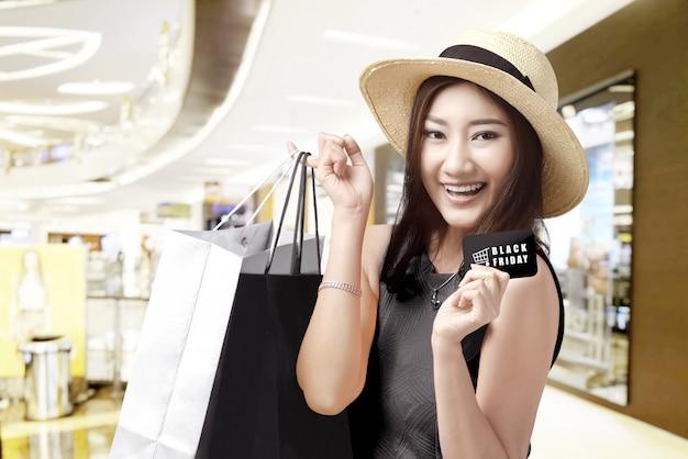 Aziatische vrouw die in hoed de kaart met black friday-teksten en het winkelen zakken in het wandelgalerij houden