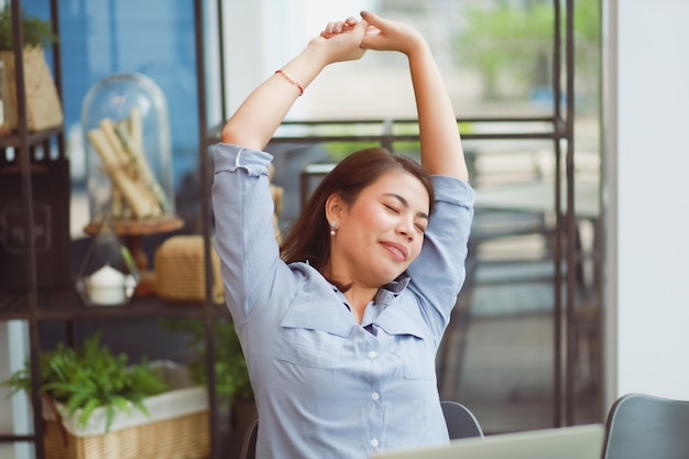 Aziatische vrouw die in koffie werkt en probleem met bureausyndroom heeft