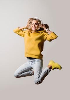 Aziatische vrouw die in studio springt
