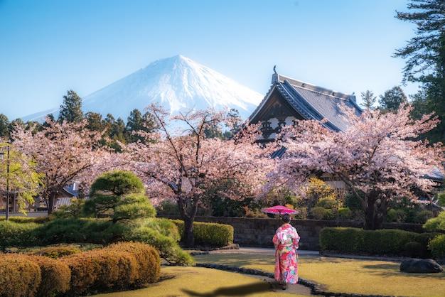Aziatische vrouw die in tempel met mt. fuji in japan