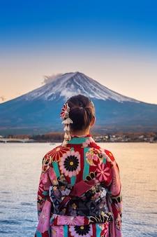 Aziatische vrouw die japanse traditionele kimono draagt bij fuji-berg. zonsondergang bij kawaguchiko-meer in japan.