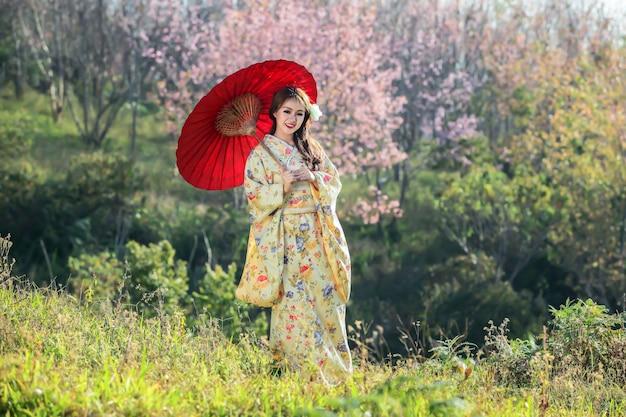 Aziatische vrouw die japanse traditionele kimono draagt bij sakuratuin.