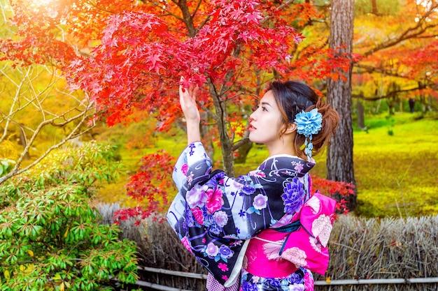 Aziatische vrouw die japanse traditionele kimono in de herfstpark draagt. japan
